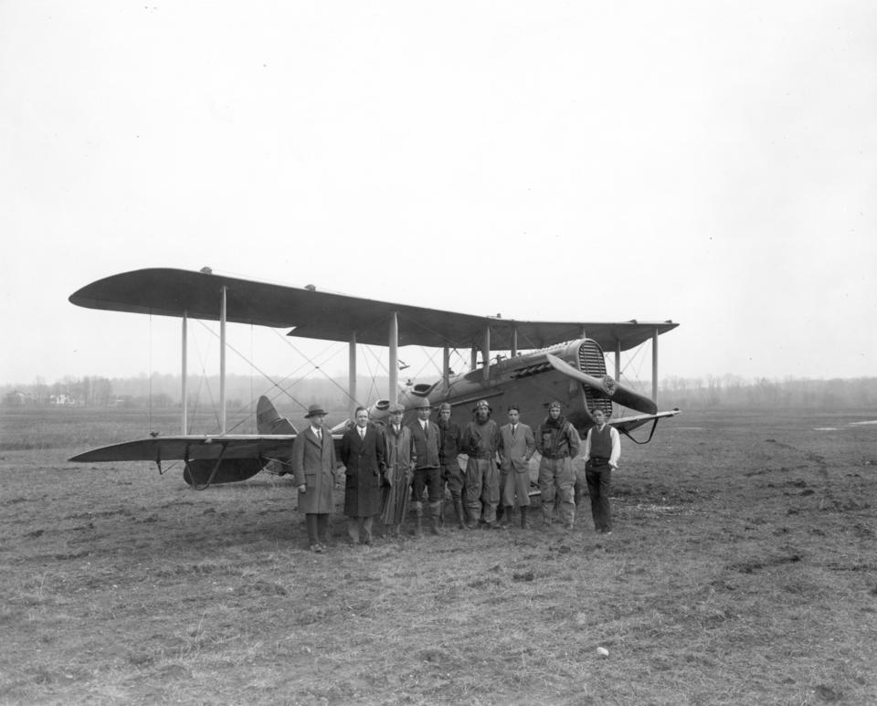 Group of people standing in front of airplane