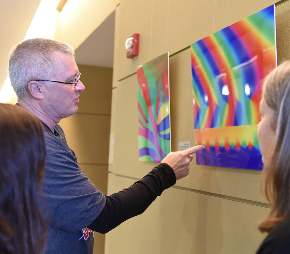 A man points out detail in a colorful image hanging in a gallery