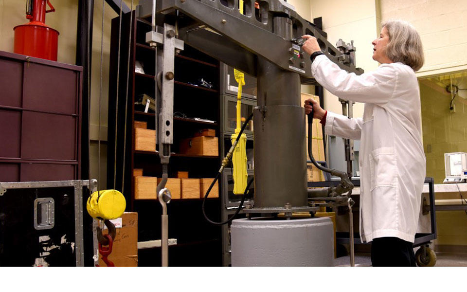 Blonde woman in white lab coat working on equipment