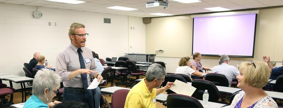 A male standing and other seated UW–Stout faculty and staff members are pictured in a classroom in an apparent discussion.