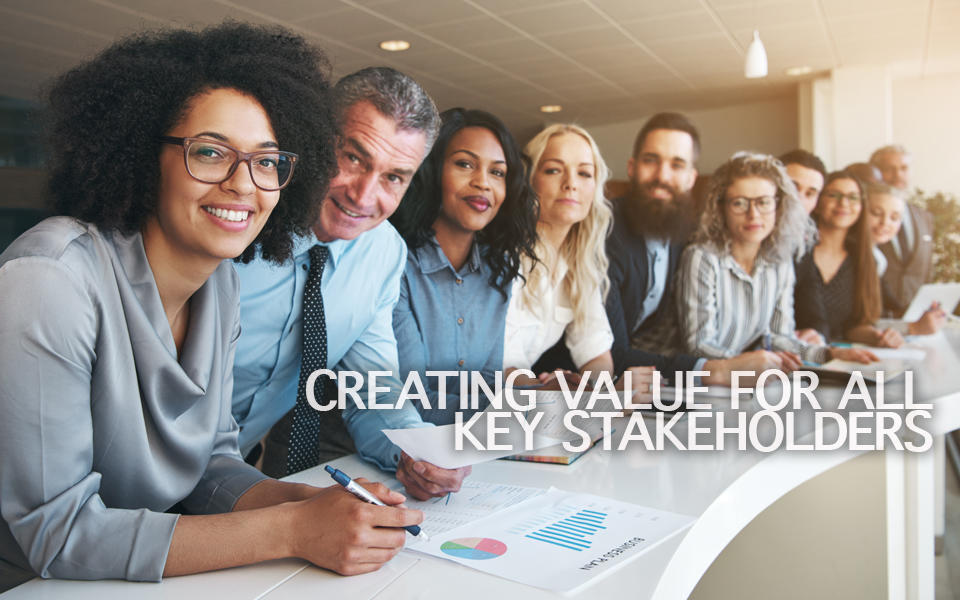 Creating Value for ALL Key Stakeholders Photo of a group of diverse employees behind a table standing together in a row in a bright office.