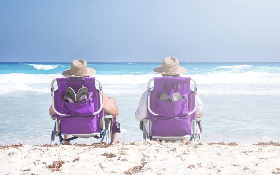 Two mature people sitting in chairs on the beach relaxing watching the ocean.