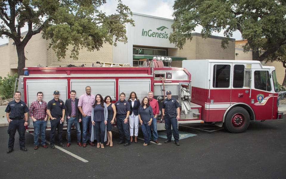 Photo of InGenesis employees in front of fire truck outside.