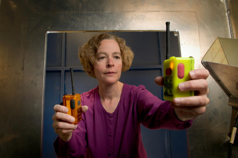 A woman holds two devices that look like colorful walkie-talkies.