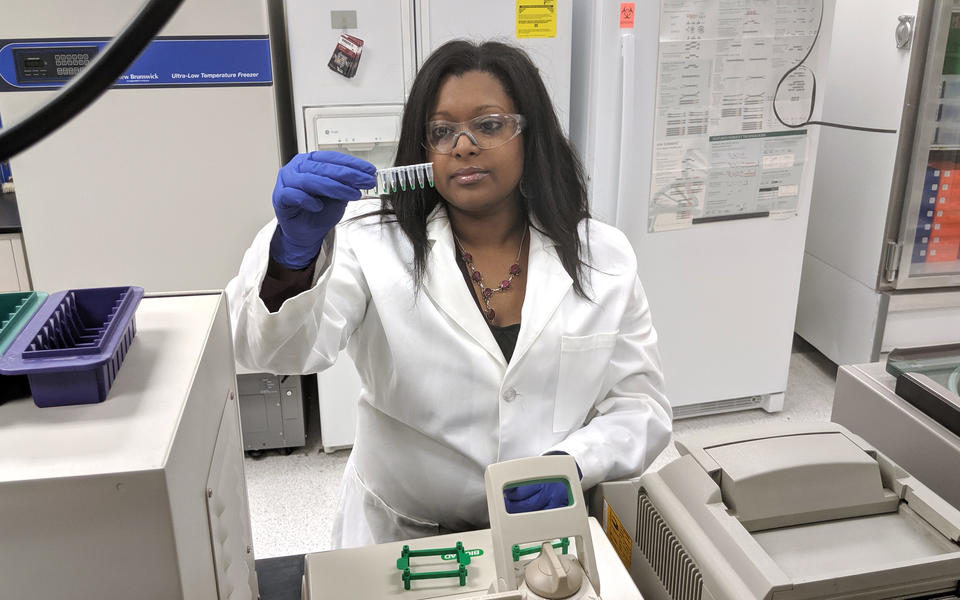 young woman in a lab coat looks at vials with a small amount of green liquid in them before putting them into a machine