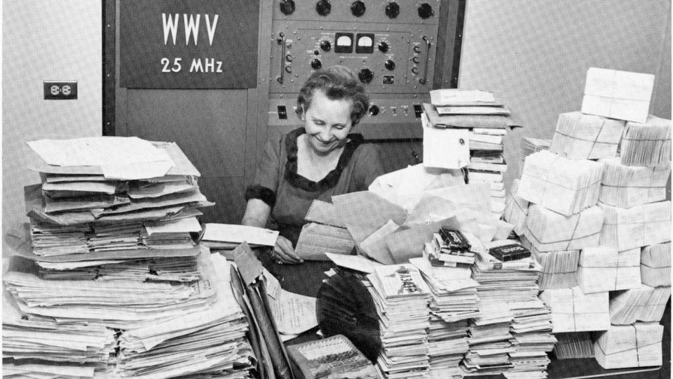 "a woman sitting in front of a control panel that reads ""WWV 2.5 MHz."" In front of her is a table covered with hundreds of letters"