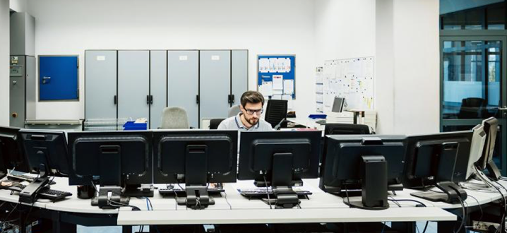 man sitting at computers in a cybersecurity center