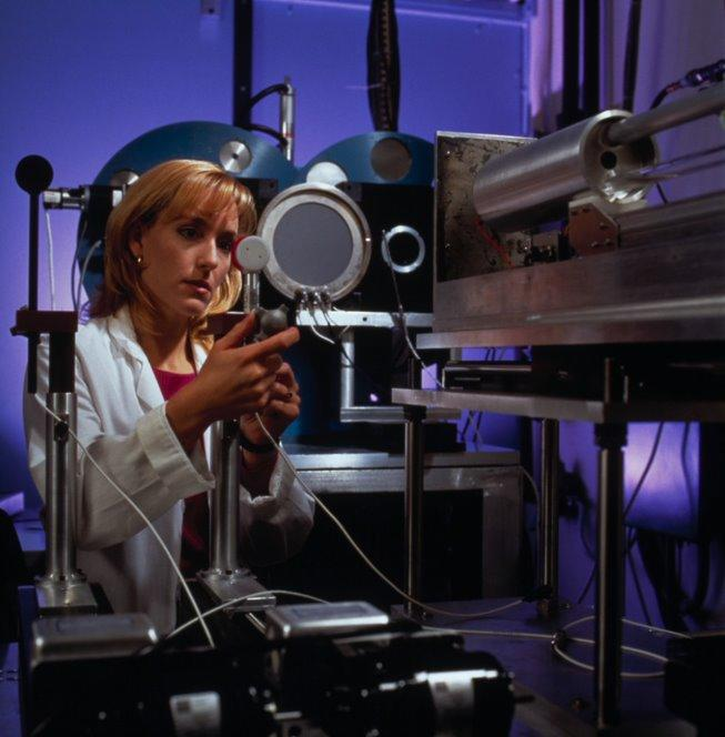 A woman in a lab coat adjusts a piece of scientific equipment