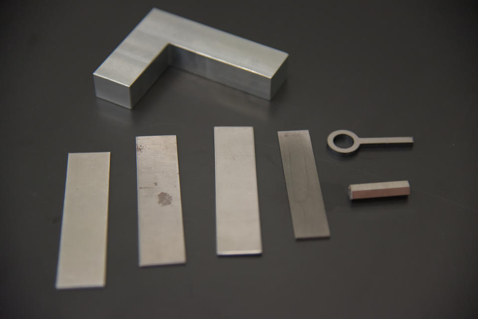 """Several rectangular pieces of flat metal, a fake key and a rectangular """"gun shaped"""" piece of metal are arranged on a table."""