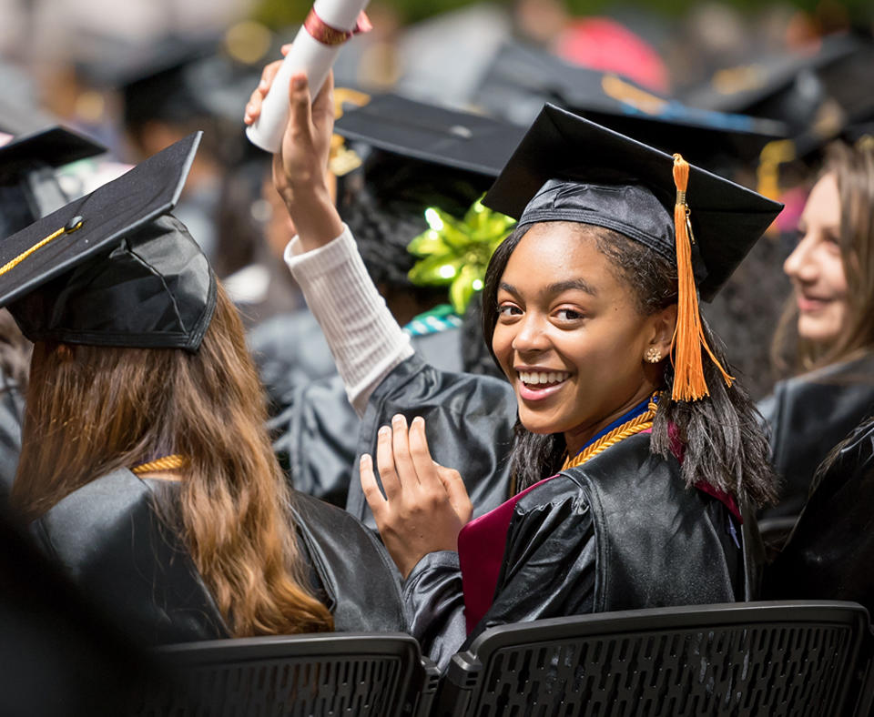 A female student at Howard Community College Commencement turning behind in her seat and smiling while holding up her diploma.
