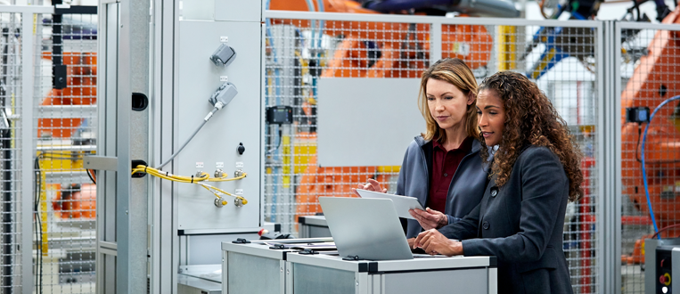 two women looking at a laptop in a manufacturing facility with robots