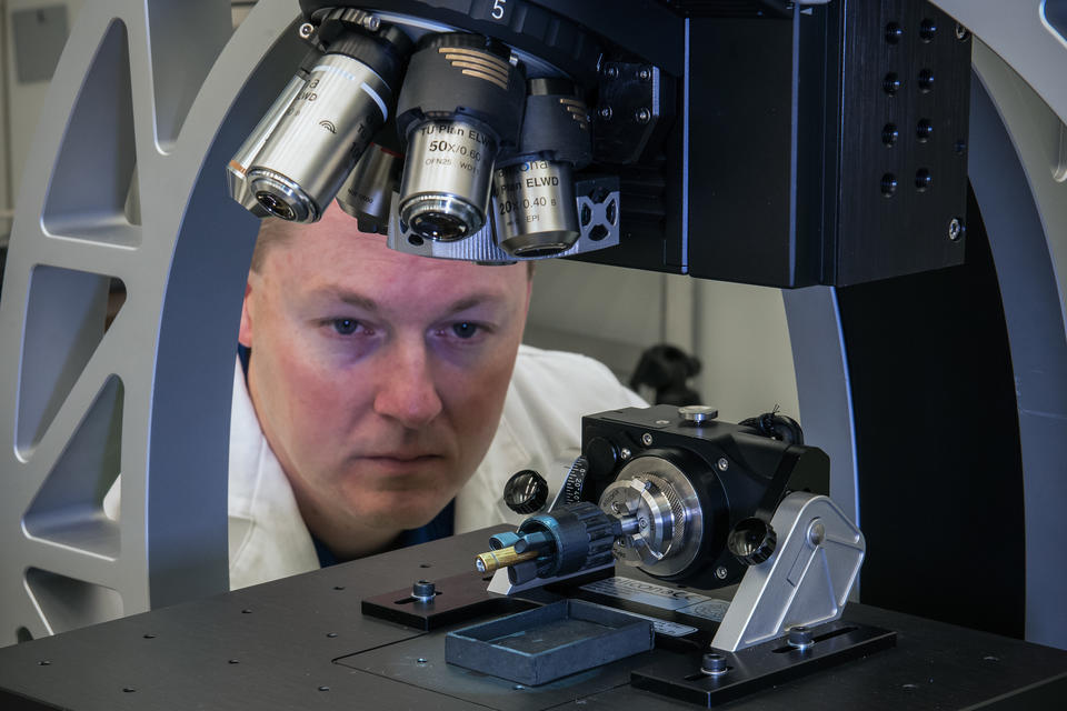 A man looks at the sample held under a microscope.