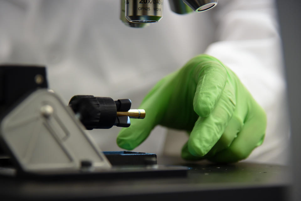 Person wearing green glove reaches under microscope to remove sample.
