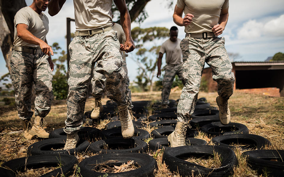 soldiers running through a tire obstacle at boot camp
