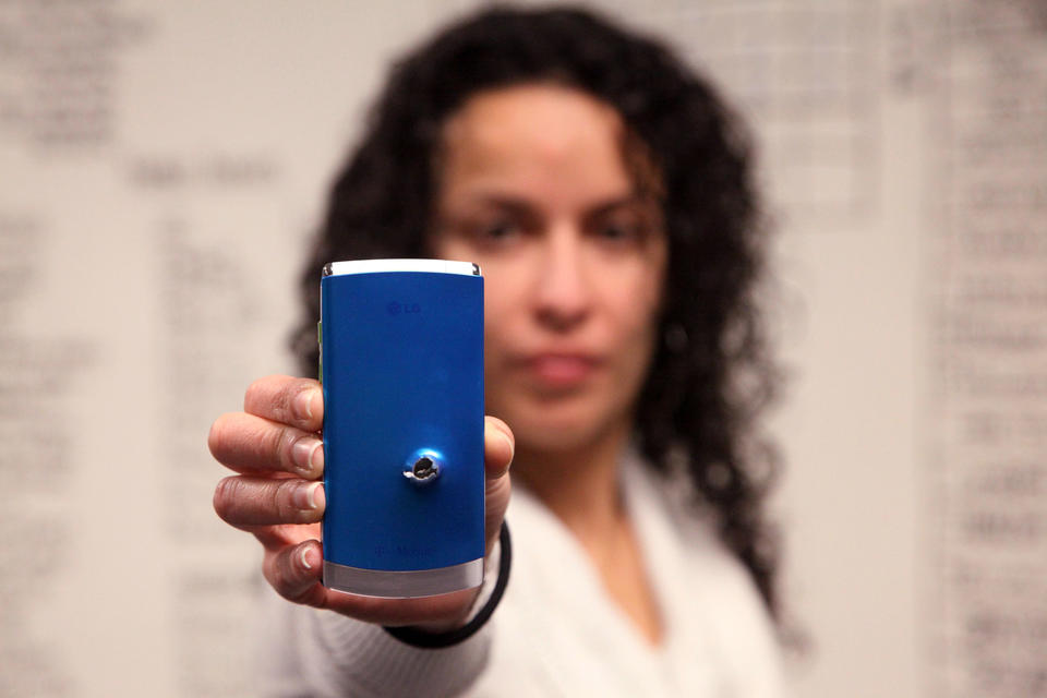 A woman holds a cellphone with a bullet hole in it.