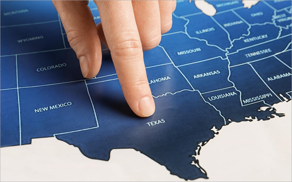 Person pointing finger on the state of texas on U.S. map.