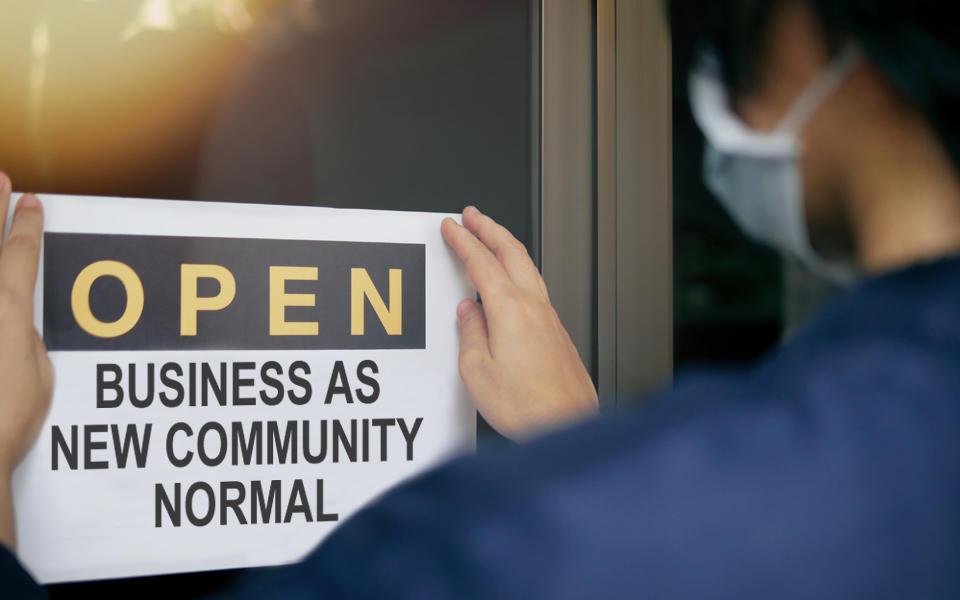 Person wearing a mask posting a sign on a glass door that says Open Business As New Community Normal