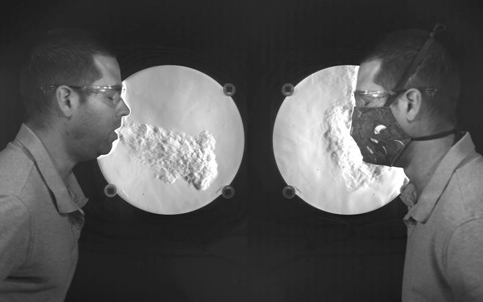 two photos of Matt Staymates facing each other in front of a schlieren camera system. On the left, Matt is not wearing a mask, on the right he is. In both photos he is coughing. In the unmasked photo, you can see a big plume of air exiting forward like a jet from his mouth. In the masked photo, the air plume hangs around his face and does not go very far.