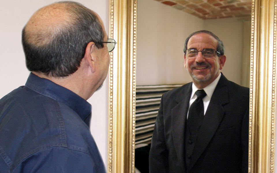 Photo of Harry Hertz looking at a reflection in the mirror of his doppelgänger in a tuxedo.