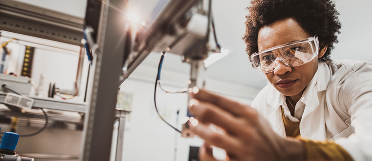 Black female engineer working on industrial machine in a laboratory