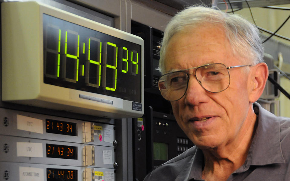 NIST physicist Judah Levine with the NIST time scale, a digital clock face reading 14:33:34 and a bank of atomic clocks.
