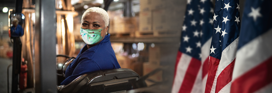 Portrait of female worker driving forklift in warehouse in a face mask
