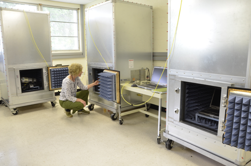 """Researcher Kate Remley examines the middle chamber containing a repeater unit in a \""""one hop\"""" communications test. The PASS is in the cabinet at left, and the base station is in the cabinet at right."""