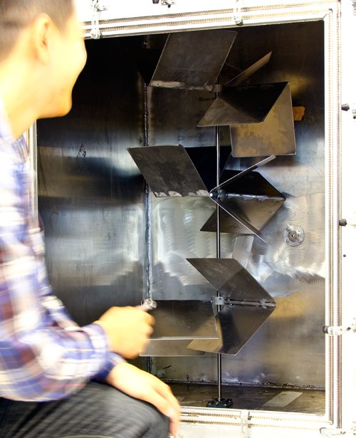 A researcher leans in to adjust the configuration of a controllable reflectivity chamber.