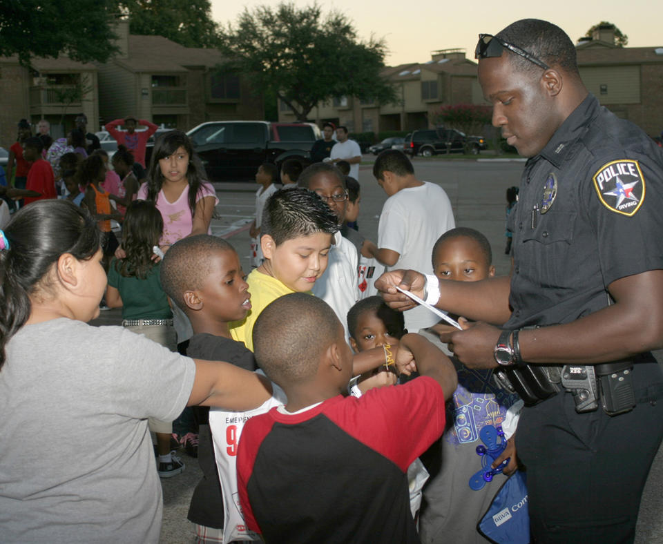 City of Irving, Texas photo of police officer talking to kids in the neighborhood.
