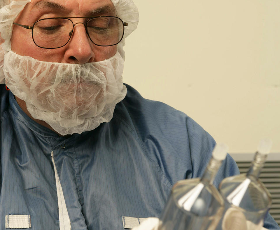 MEDRAD photo of employee holding glass containers in a lab.