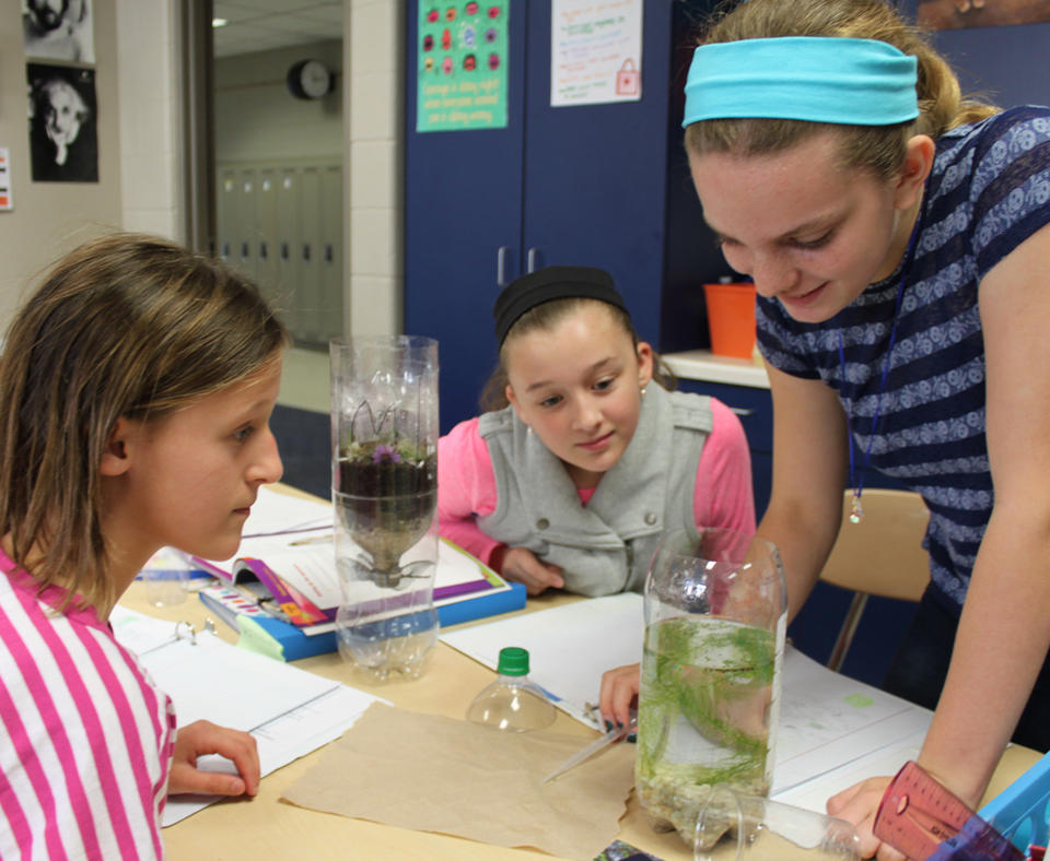 Pewaukee School District photo of three students doing science experiment.