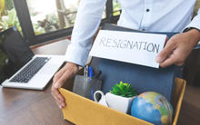 Employee holding a resignation letter with a box of their belongings.