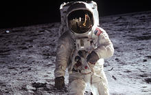 Photo of man in white space suite on surface of moon at night.