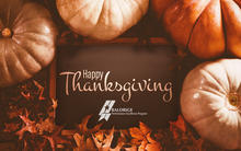 Happy Thanksgiving from the Baldrige Program showing a rustic background with pumpkins and autumn leaves.