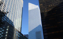 white office building with a wedge top among other skyscrapers