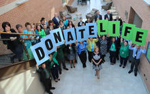 CORE staff celebrates National Blue & Green Day at their headquarters in Pittsburgh, PA by holding up signs spelling Donate Life.