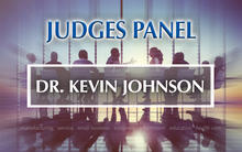 Baldrige Judges Panel Dr. Kevin Johnson with a background panel of people having a discussion.