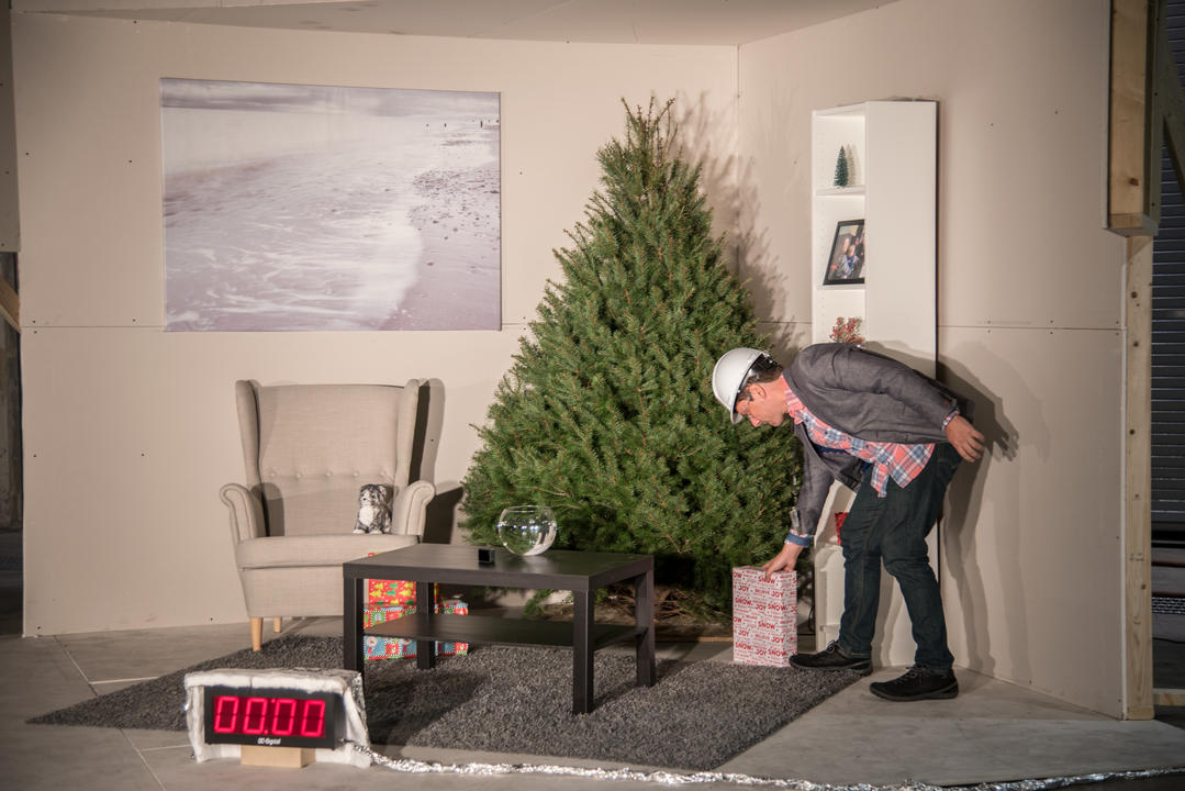 NIST employee places a Christmas present under an undecorated Christmas tree