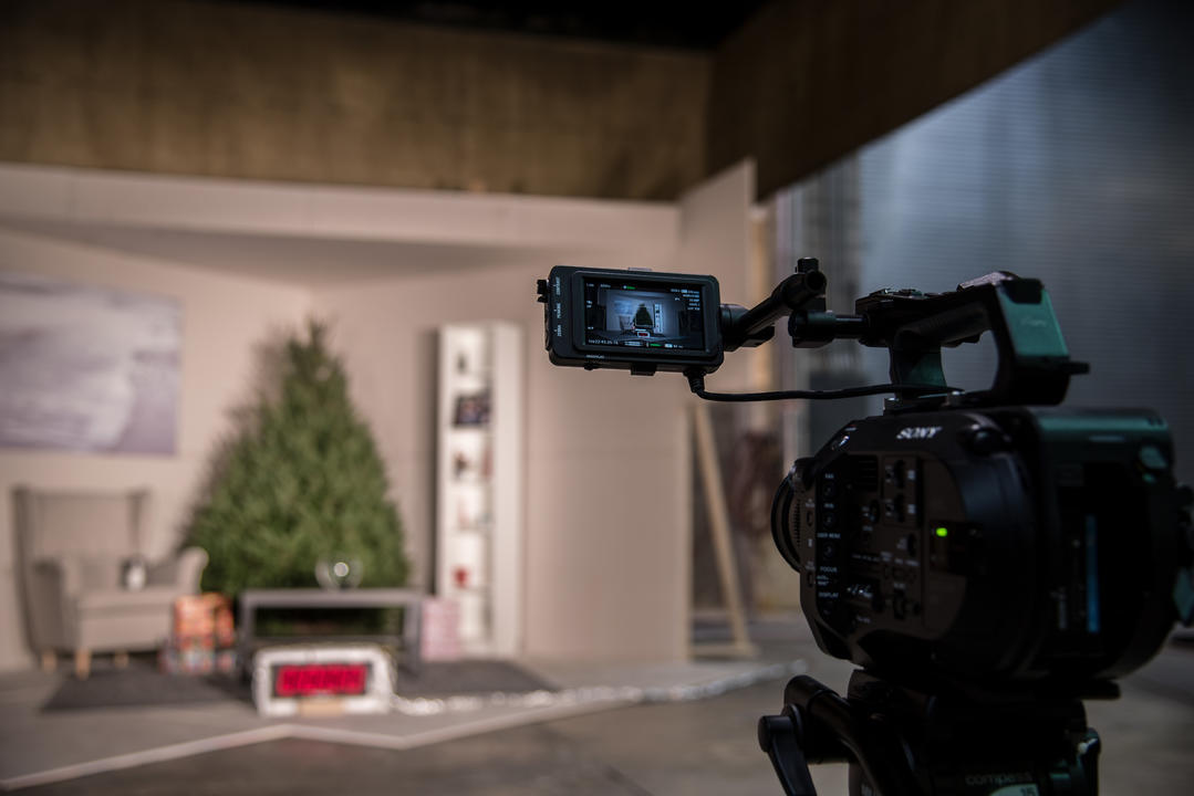Video camera aimed at a room with a Christmas tree, bookshelf, coffee table and chair