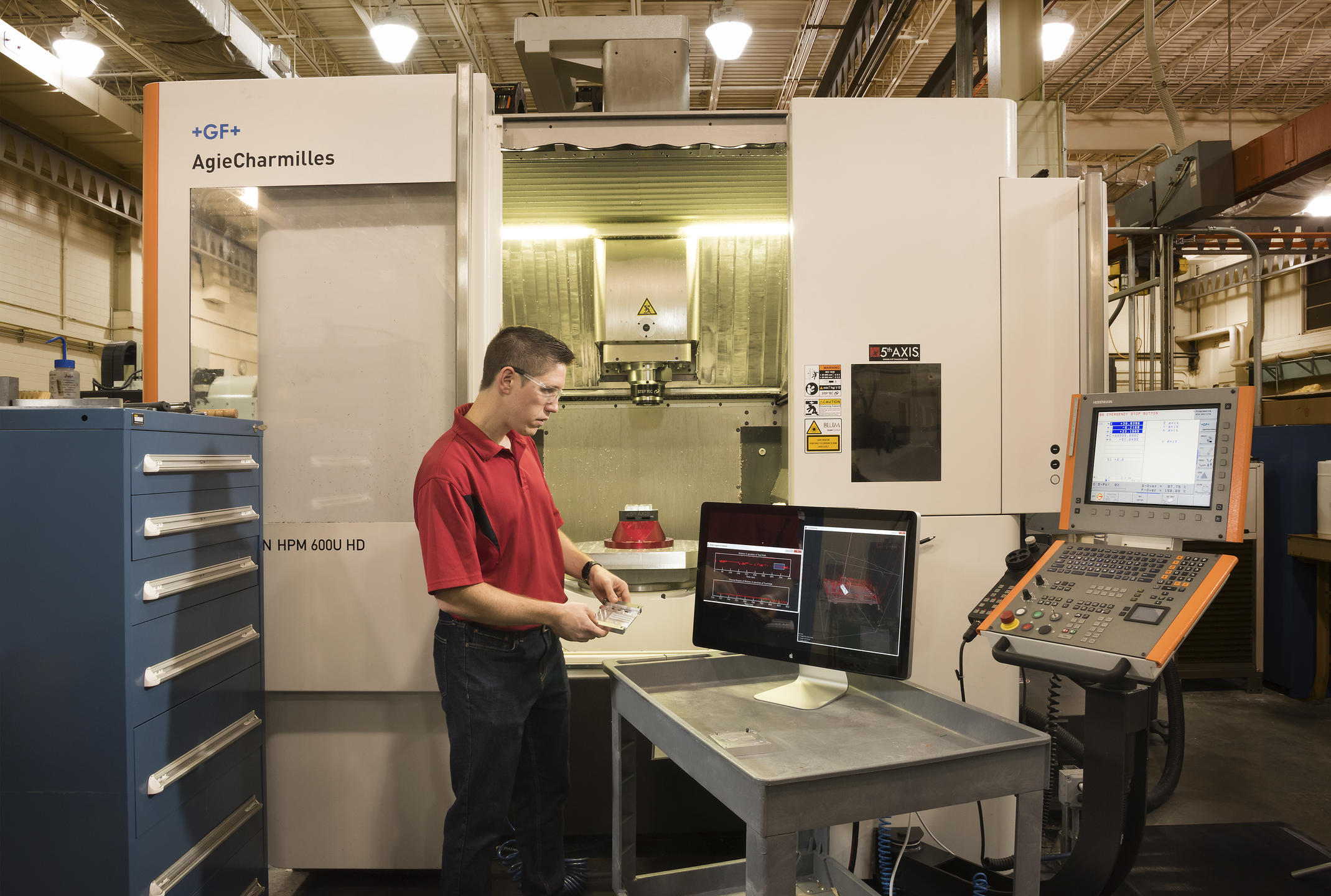 NIST researcher Tom Hedberg in a machine shop with computer monitor displaying CAD image