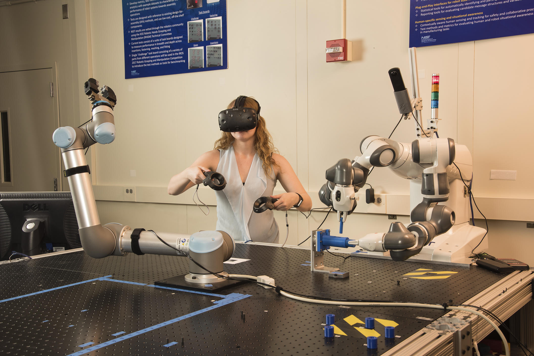 Researcher Megan Zimmerman wearing a virtual reality headset and handheld devices to control 2-handed tasks of a robot
