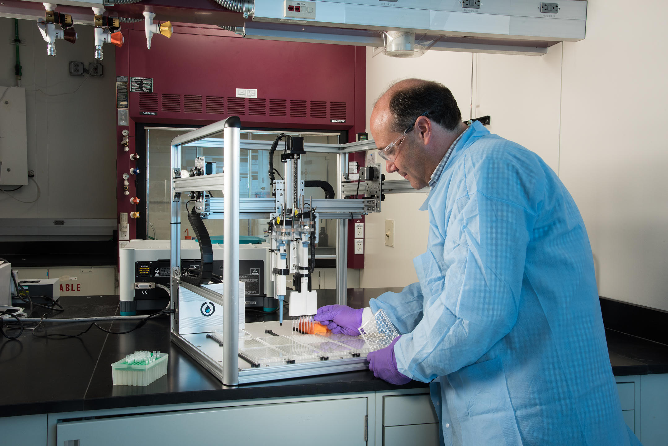 Researcher John Elliott in the lab loading samples into automated liquid handling instrument.