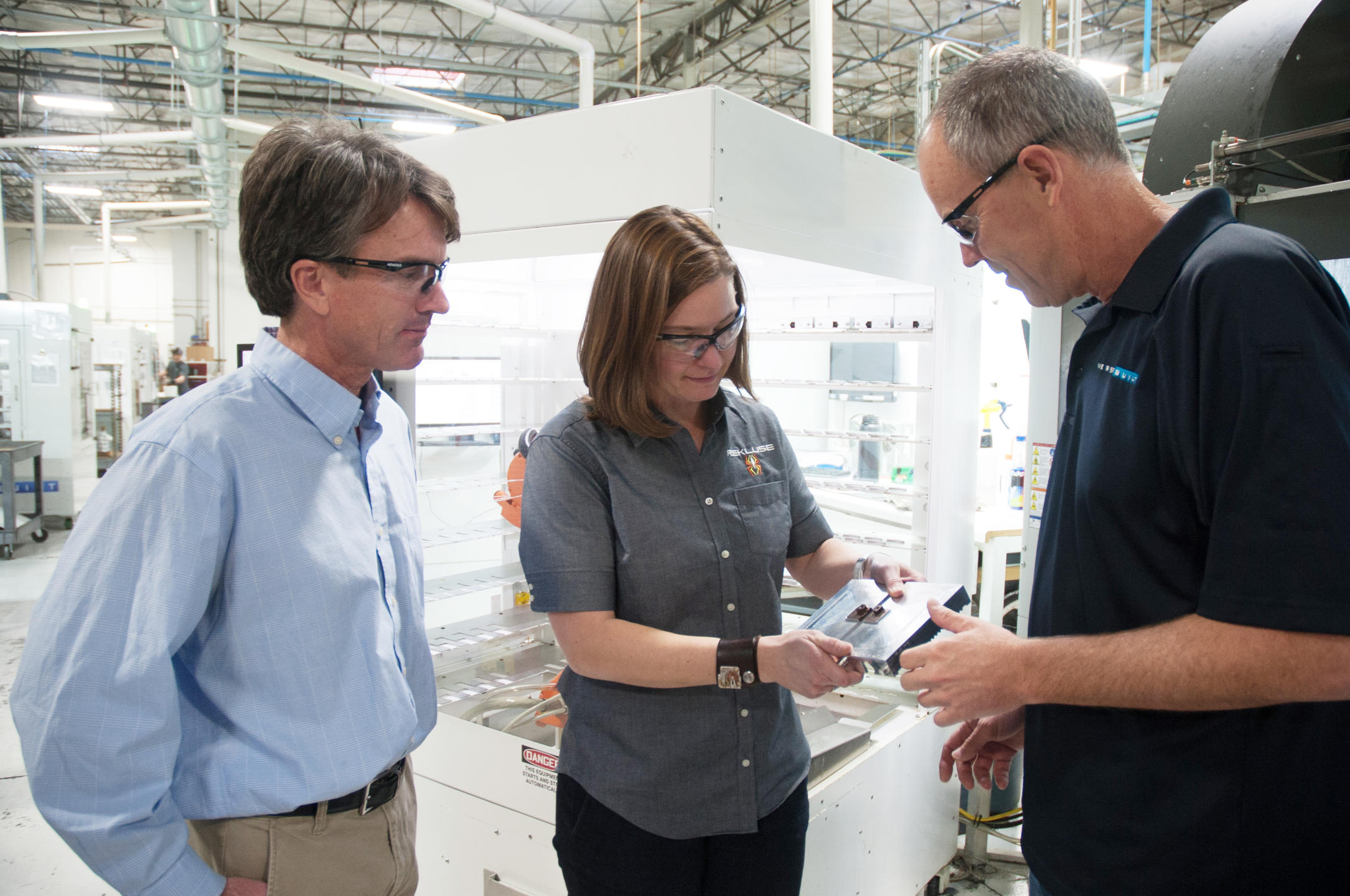 Three people on a manufacturing floor discussing a new product