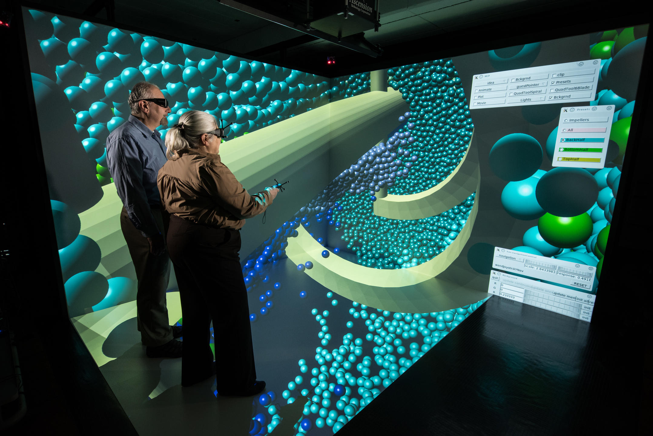 Researchers wearing virtual reality headsets in the CAVE, with concrete particles on display