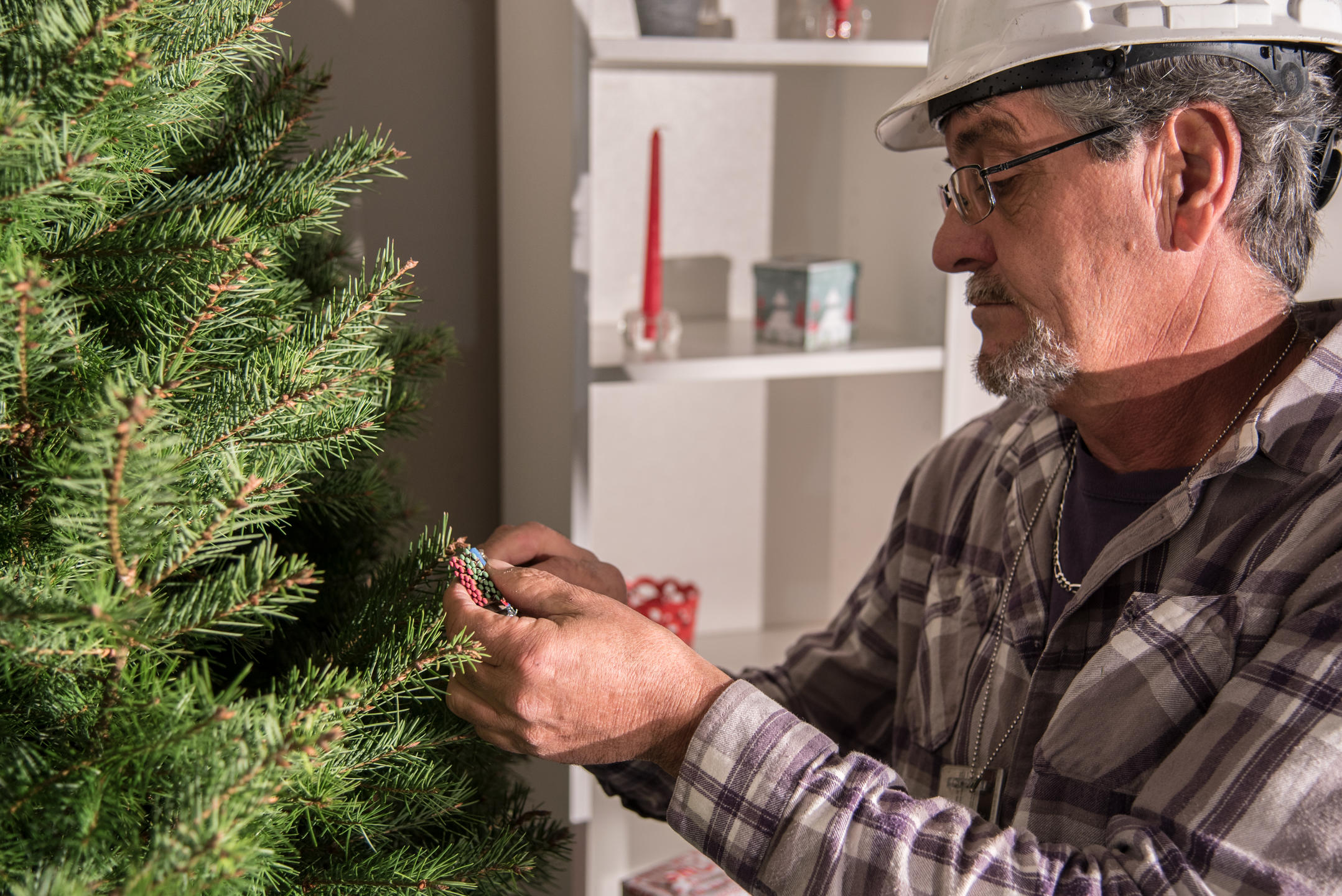 NIST technician placing a book of matches into a Christmas tree