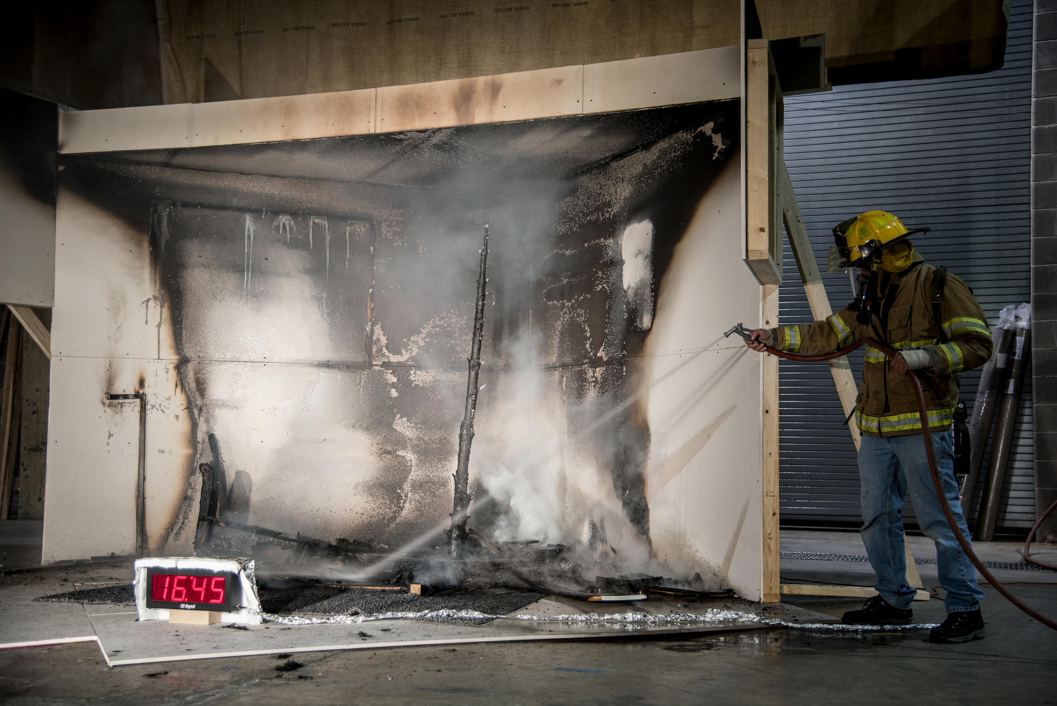 NIST employee spraying water to put out a fire
