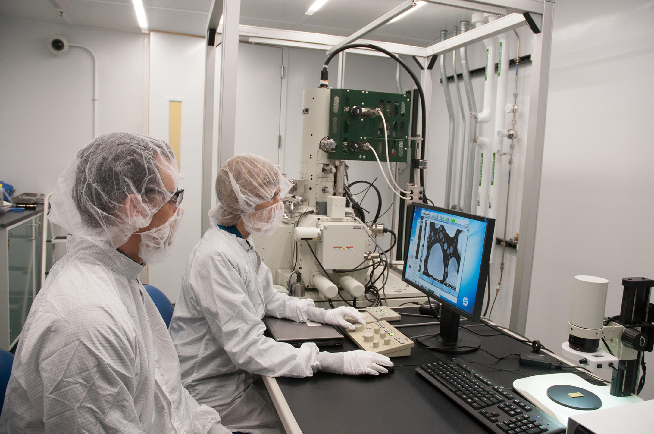 Two seated people in bunny suits look at a bluish computer image