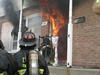 Flames from a living-room pour out the front door of a townhouse during a NIST test.