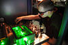 Photo of UC graduate student Matt Kirchner fine-tuning an ultra-stable microwave generator at NIST