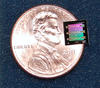 NIST's superconducting circuit containing a 'micro drum' sitting atop of a penny to show how much smaller it is.